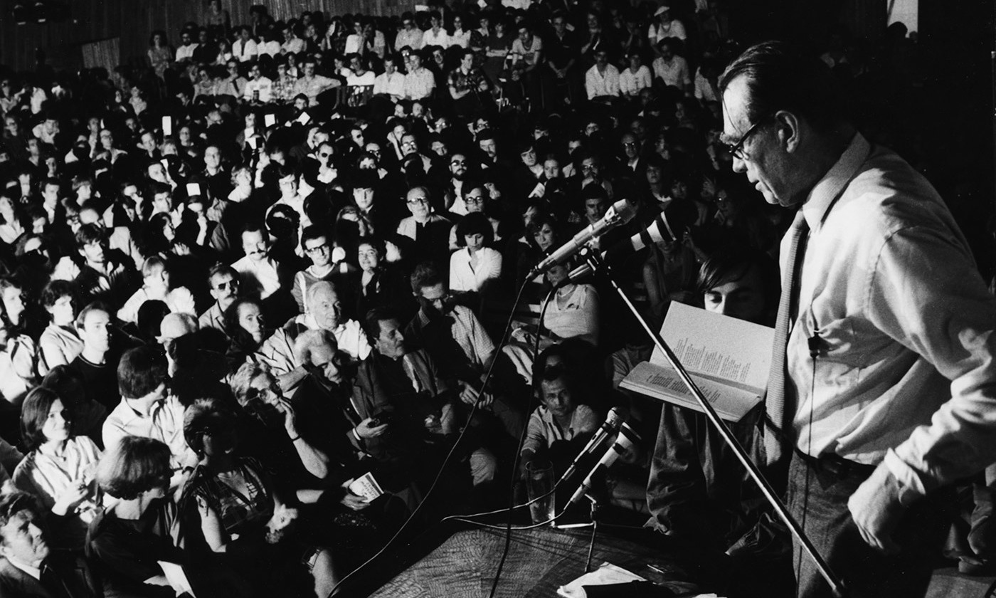 Poet and Nobel Prize winner Czesław Miłosz speaking onstage to a crowd of students at Warsaw University, Poland, 1981. <em>Photo by Keystone/Getty</em>