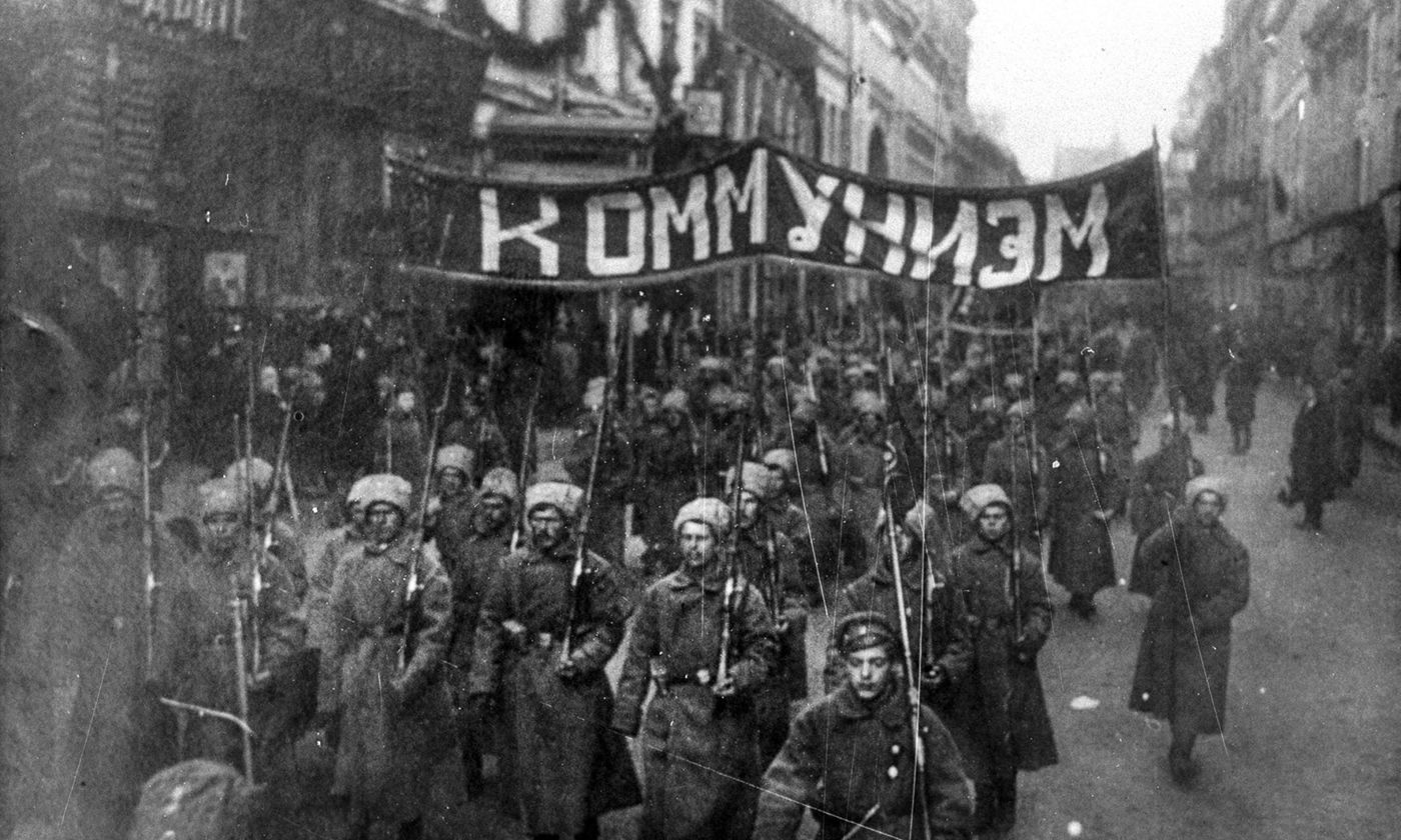 <p>Armed soldiers carry a banner reading 'Communism' in Nikolskaya street, Moscow, October 1917. <em>Courtesy Wikipedia</em></p>