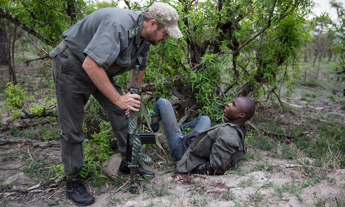 A member of the military-style Special Ranger Patrol talks to a suspected rhino poacher on 7 November 2014 at the Kruger National Park, South Africa. <em>Photo by James  Oatway/Sunday Times/Getty</em>