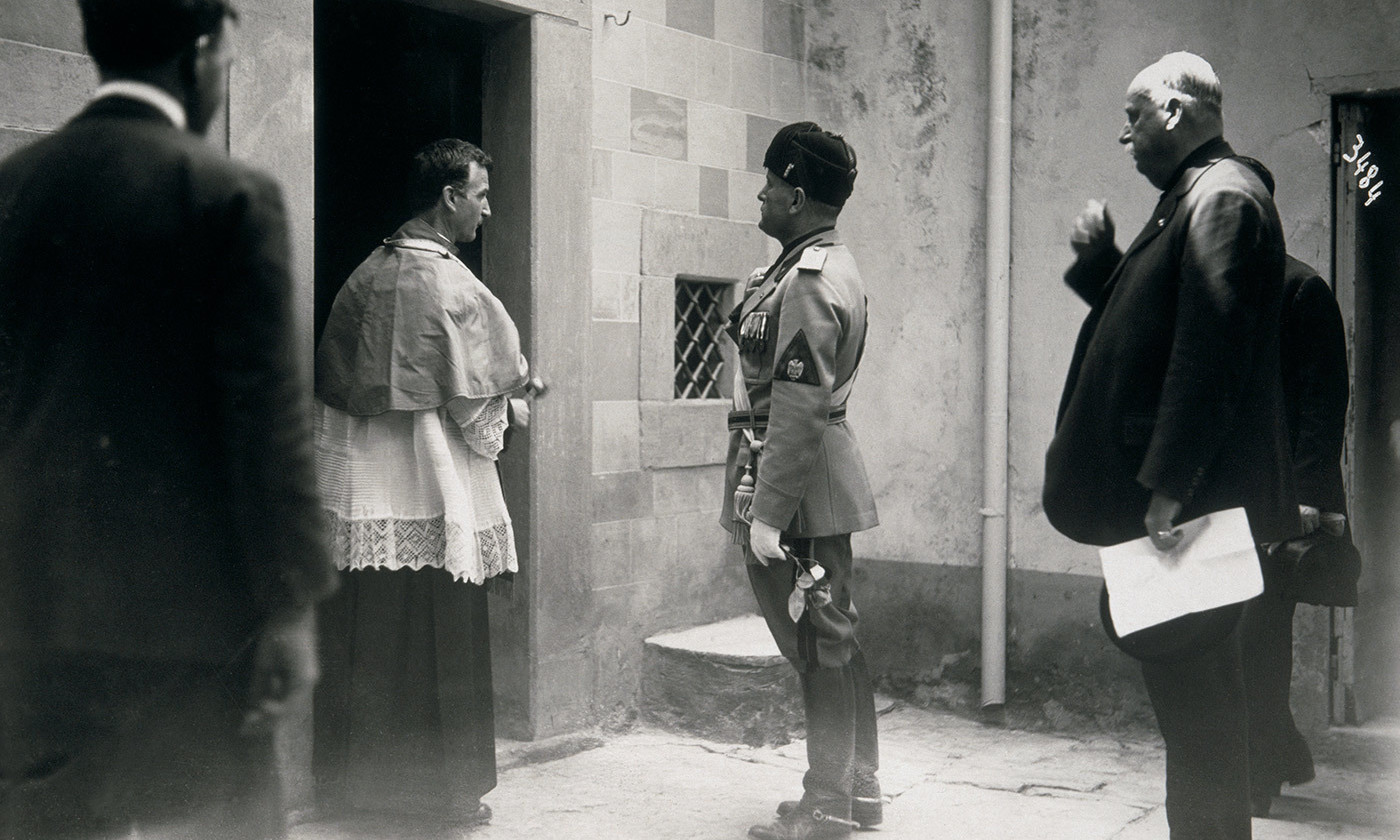 <p>Under threat; Mussolini attends chapel while on a visit to an estate in Bagno a Ripoli owned by Count Piero Ginori. <em>Photo by Corbis/Getty</em></p>