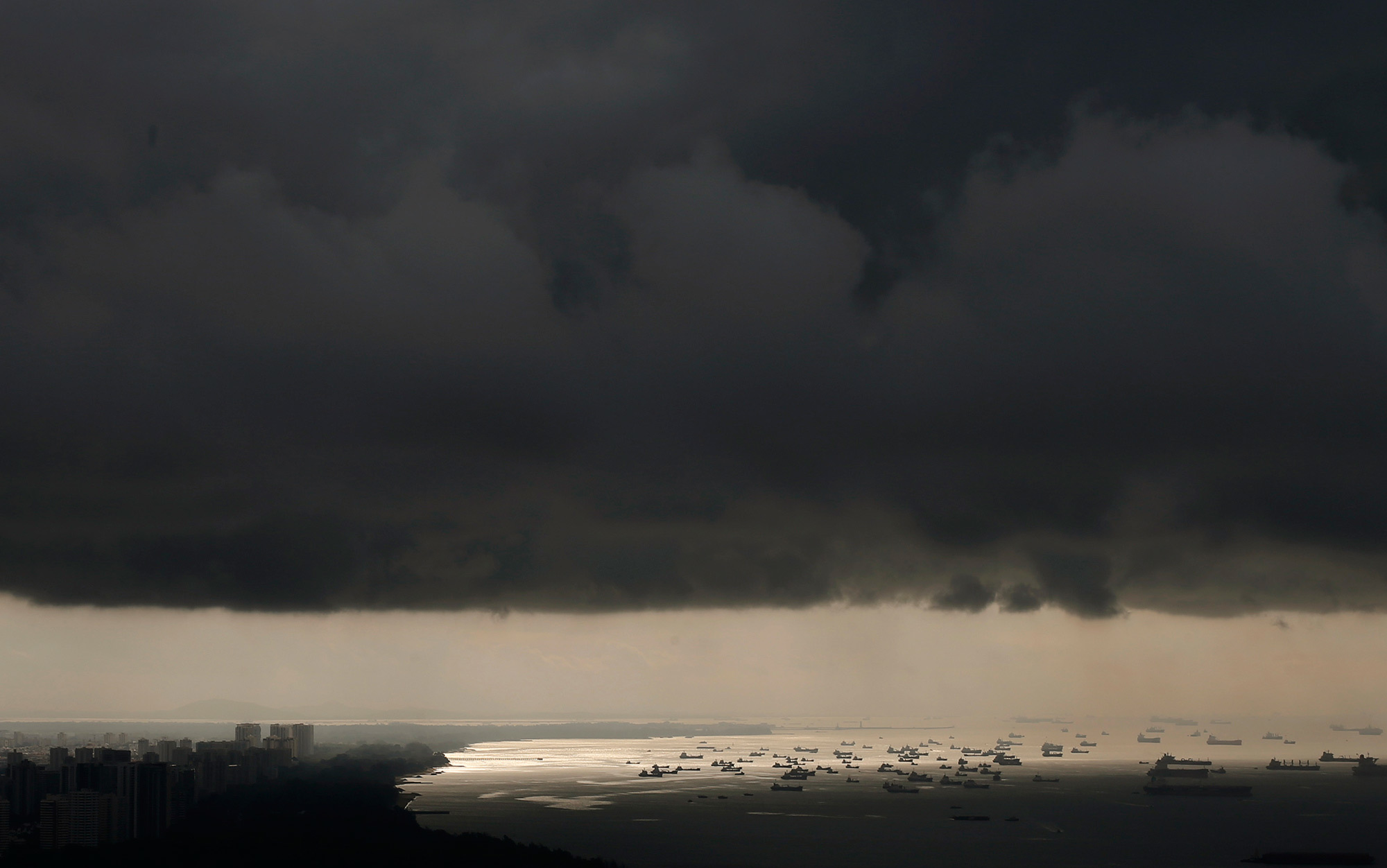 Resultado de imagem para Storm clouds gather above ships waiting to dock in Singapore.